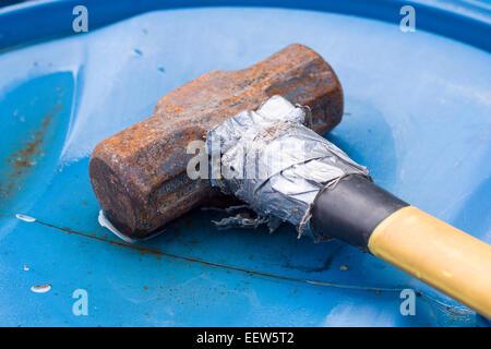 Marteau rouillé fixé avec du ruban adhésif. Un traîneau rouillé repose sur un baril de plastique bleu. Sa poignée Banque D'Images
