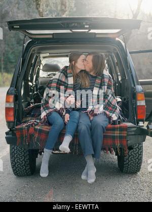Jeune couple assis dans l'arrière de leur voiture, en l'embrassant. Banque D'Images