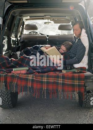 Jeune couple couché dans l'arrière de leur voiture, la lecture d'un livre. Banque D'Images