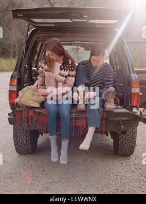 Jeune couple assis dans l'arrière de leur voiture, de mettre des bottes. Banque D'Images