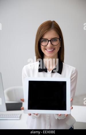 Smiling businesswoman montrant l'écran de l'ordinateur tablette Banque D'Images
