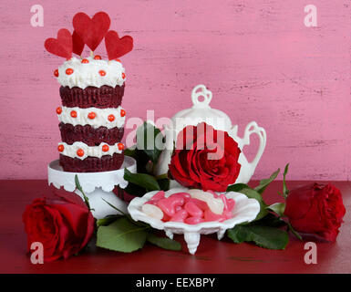 Triple couche style vintage red velvet cupcake on white cake stand avec des roses et des bonbons contre un arrière Banque D'Images