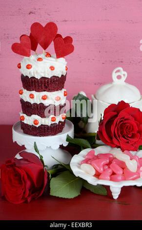 Triple couche style vintage red velvet cupcake on white cake stand avec des roses et des bonbons contre un fond Banque D'Images