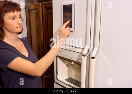 Jeune femme Utilisation du bloc on web activé réfrigérateur internet des objets appareil dans la cuisine Banque D'Images