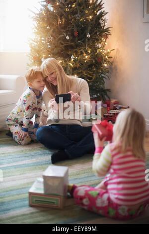 Mère avec enfants (4-5, 6-7) l'ouverture des cadeaux de Noël et de prendre des photos Banque D'Images