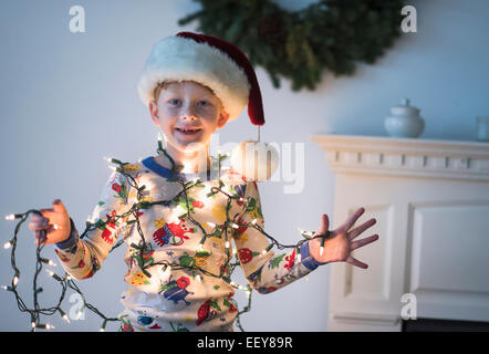 Portrait of boy (6-7) holding christmas lights Banque D'Images