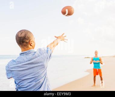 USA, Floride, Jupiter, les jeunes hommes jouent au football sur la plage Banque D'Images
