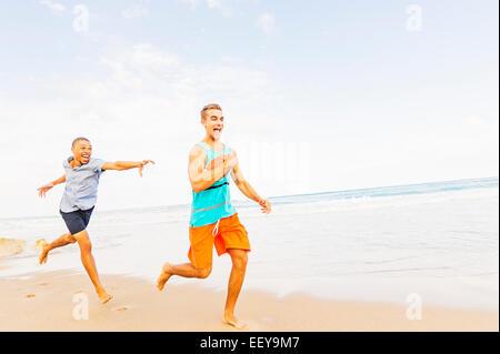 USA, Floride, Jupiter, les jeunes hommes jouant avec football on beach Banque D'Images