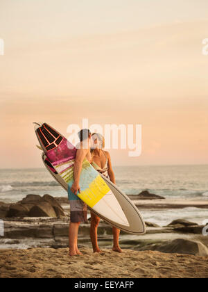 États-unis, Californie, Laguna Beach, Mid-adult couple kissing on beach at sunset Banque D'Images