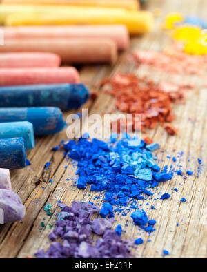 Collection de couleur arc-en-ciel avec craies pastel craie écrasée sur le vieux bureau en bois. Banque D'Images