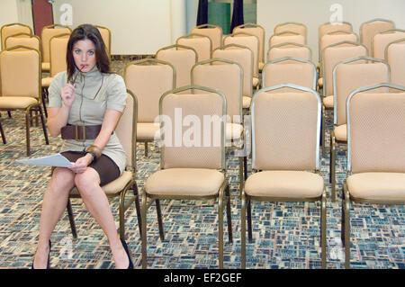 Femme seule dans une salle de conférence Consultation des notes Banque D'Images