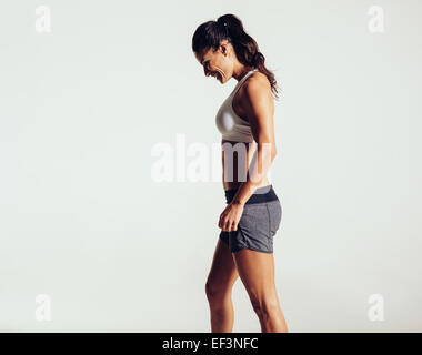 Vue latérale d'happy young woman in sports wear contre fond gris. Femme en riant de remise en forme. Banque D'Images
