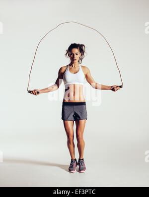 Jeune femme fit corde à sauter. Portrait of muscular young woman jumping rope sur fond blanc gris. Banque D'Images