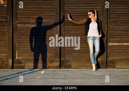 Jeune femme gesticulant avec silhouette de jeune homme contre le mur en bois Banque D'Images