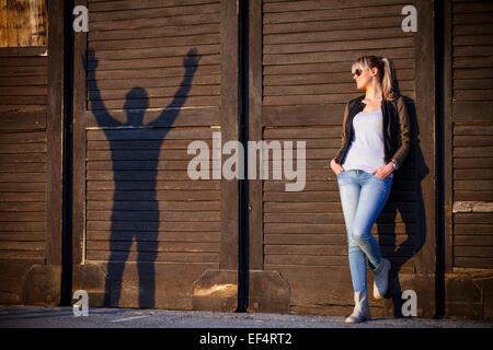 Jeune femme aux côtés de silhouette de jeune homme contre le mur en bois Banque D'Images
