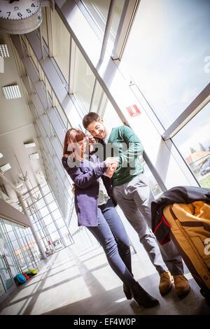 Jeune couple en bâtiment de l'aéroport de vérifier le temps Banque D'Images