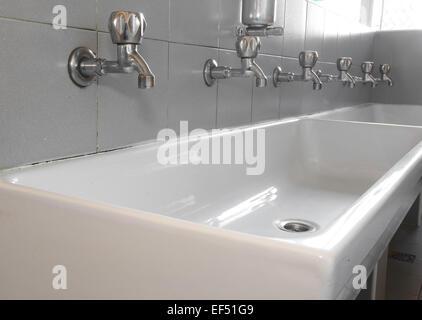 Série de robinets en acier dans l'évier en céramique blanche Banque D'Images