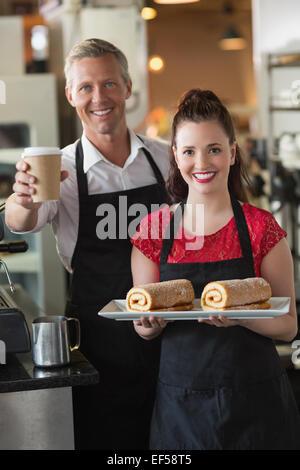 Waitress smiling at the camera montrant des gâteaux Banque D'Images
