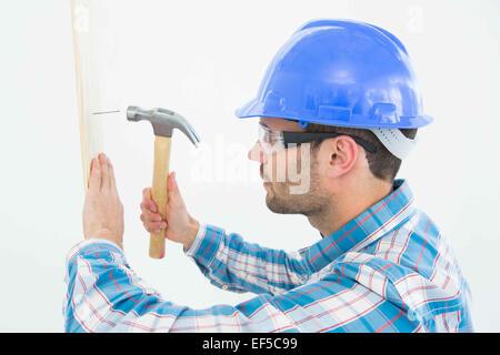 Carpenter hammering nail sur planche en bois