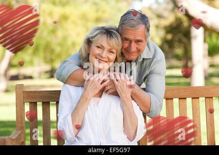 Image composite du vieil homme serrant sa femme qui est sur le banc Banque D'Images