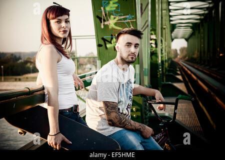 Jeune couple avec Skateboard and BMX bicycle outdoors