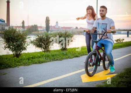 Jeune couple de la planche à roulettes et le vélo ensemble