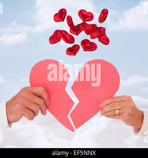 Image composite du couple holding a broken heart papier Banque D'Images