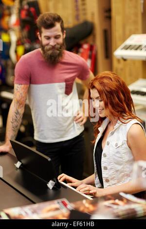 L'homme et la femme à jouer du piano à music store Banque D'Images