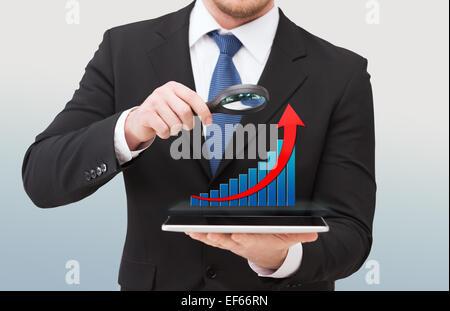 Businessman holding loupe sur tablet pc Banque D'Images