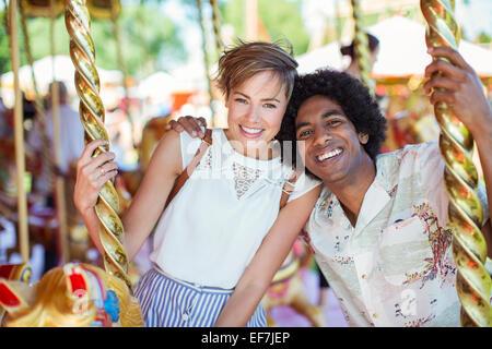 Jeune couple multiracial sur carrousel en amusement park Banque D'Images