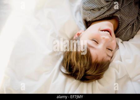 Heureux garçon couché sur le lit Banque D'Images