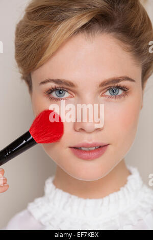 Portrait d'une femme à l'aide de make-up pinceau sur son visage