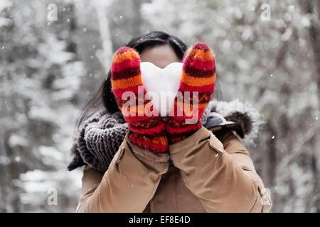 Jeune femme en rouge mitaines tenant un cœur fait de neige devant son visage, concept romantique Banque D'Images