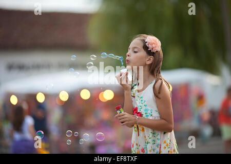 Girl (8-9) in dress soufflant des bulles de savon Banque D'Images
