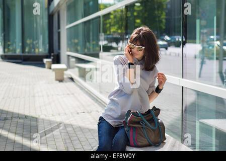 Femme à l aide d un smartphone sur la rue portant un grand foulard ... 8aa93042e34