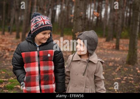 Frère et soeur (6-7) (4-5) walking in forest Banque D'Images