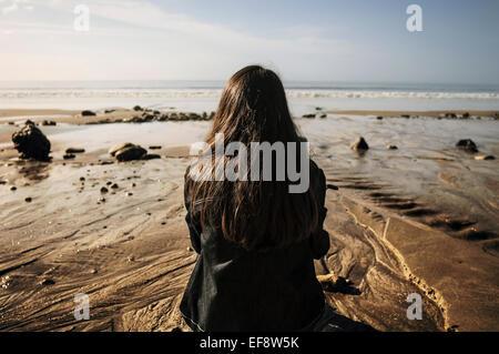 France, jeune femme assise sur le sable à la recherche en mer Banque D'Images