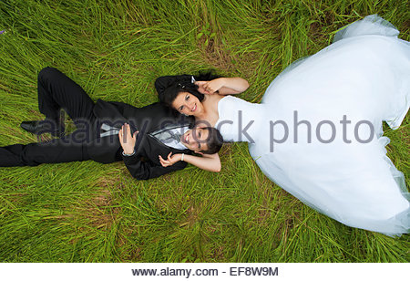 Bride and Groom lying on grass Banque D'Images