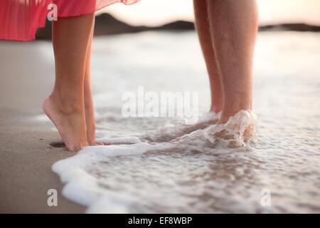 Gros plan d'un couple debout à la cheville au fond de l'eau sur la plage