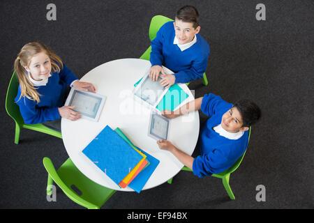 Vue aérienne des garçons et fille assise à table ronde avec les tablettes numériques, looking at camera Banque D'Images