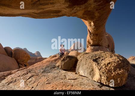 Une femme pose pour une photo sous le pont de granit, ou rock arch, à la montagne Spitzkoppe, Namibie, Afrique. Banque D'Images