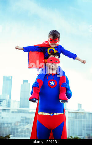 Super Héros père exerçant son fils sur les épaules sur les toits de la ville Banque D'Images