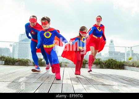 La famille de super-héros jouant sur les toits de la ville Banque D'Images
