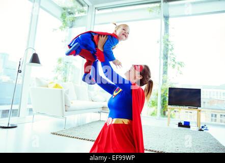 Jouer super-héros avec bébé dans la salle de séjour Banque D'Images