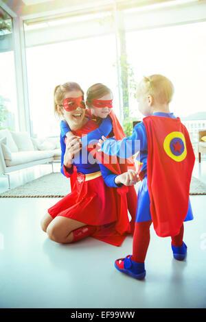 Mère de super-héros et les enfants qui jouent dans la salle de séjour Banque D'Images