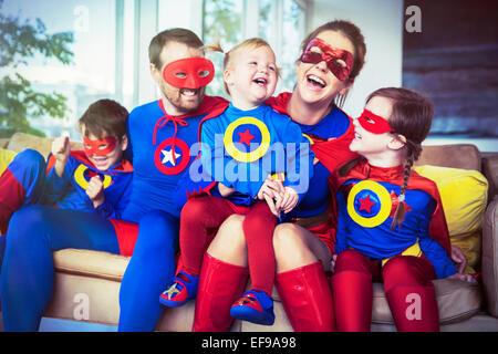 La famille de super-héros de rire sur canapé Banque D'Images