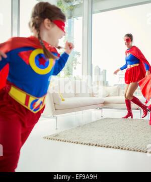 La famille de super-héros chassant les uns les autres dans la salle de séjour