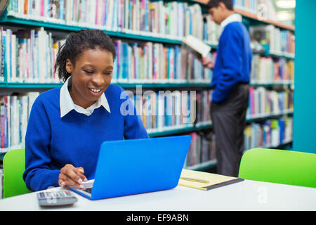 Smiling female student using laptop in library Banque D'Images