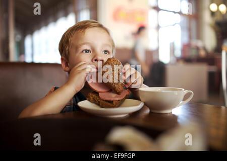 Petit enfant en train de déjeuner avec café et thé dans sandwich Banque D'Images
