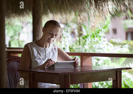 Smiling woman using tablet computer in cafe pendant ses vacances